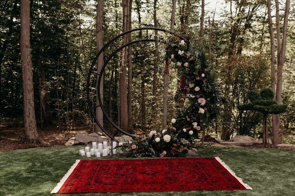 Ceremony location with red oriental rug and circular floral archway