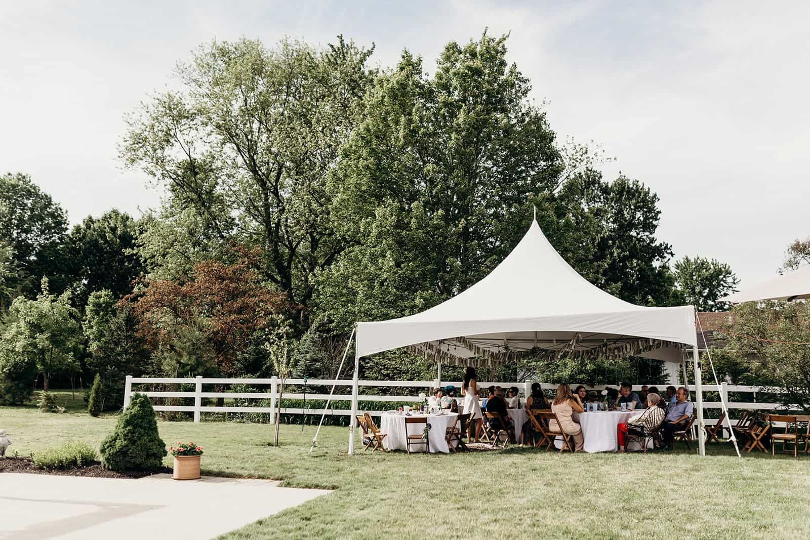 Backyard wedding tent with guests inside