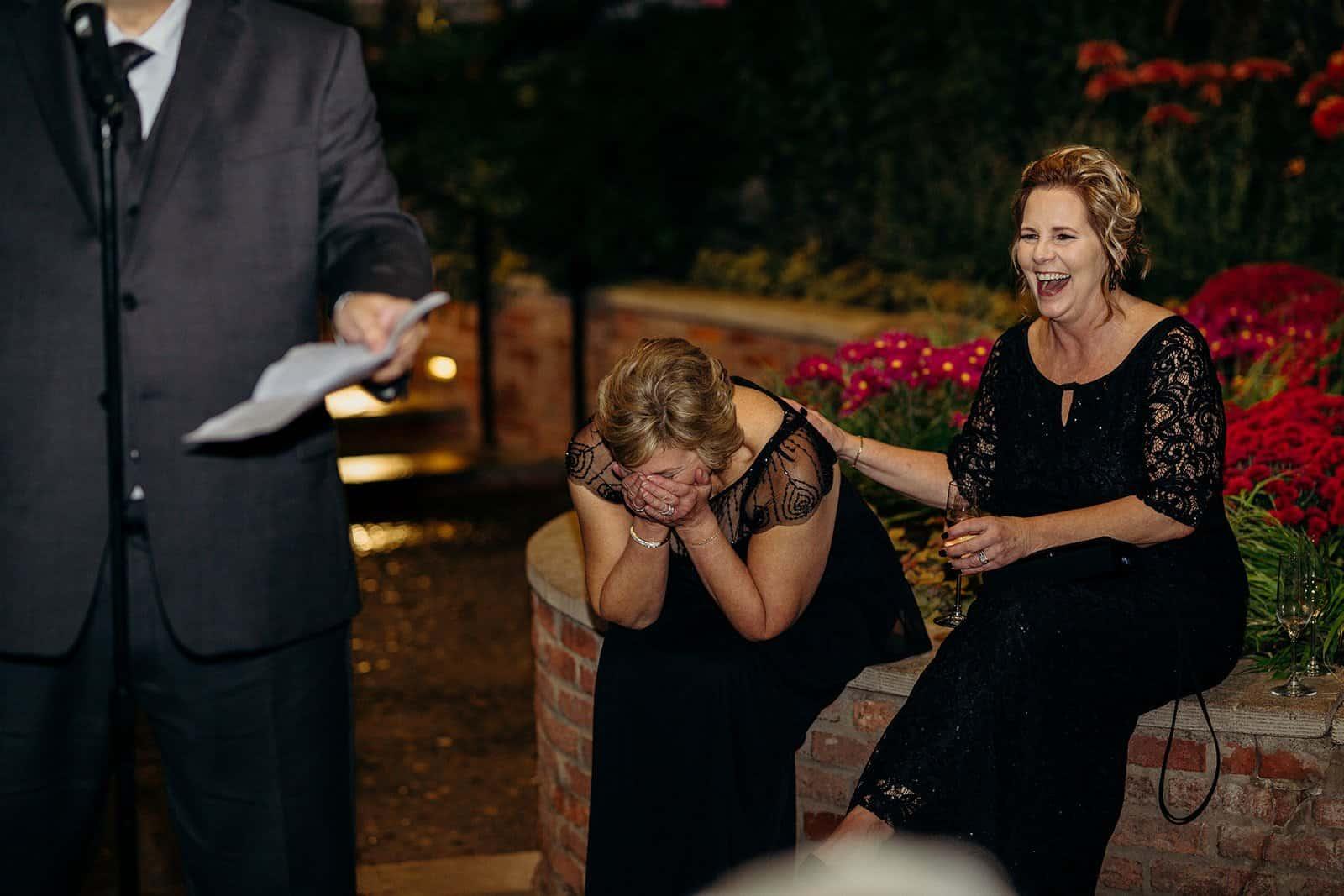 two ladies laugh while sitting on brick ledge