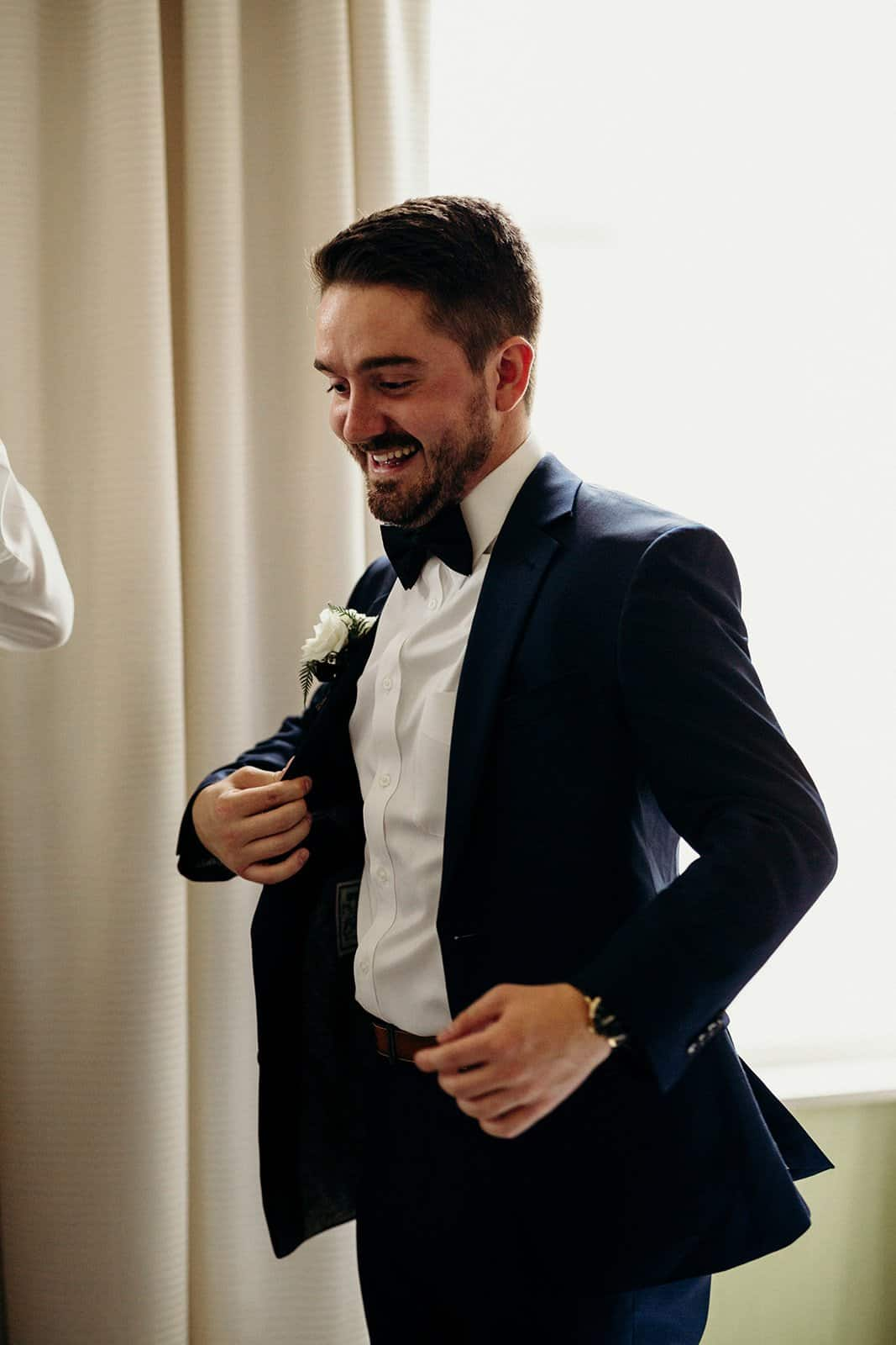 Groomsman smiles and laughs while getting ready
