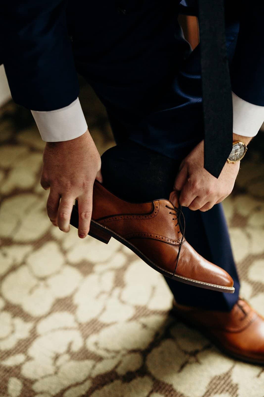 man puts on brown wedding shoes