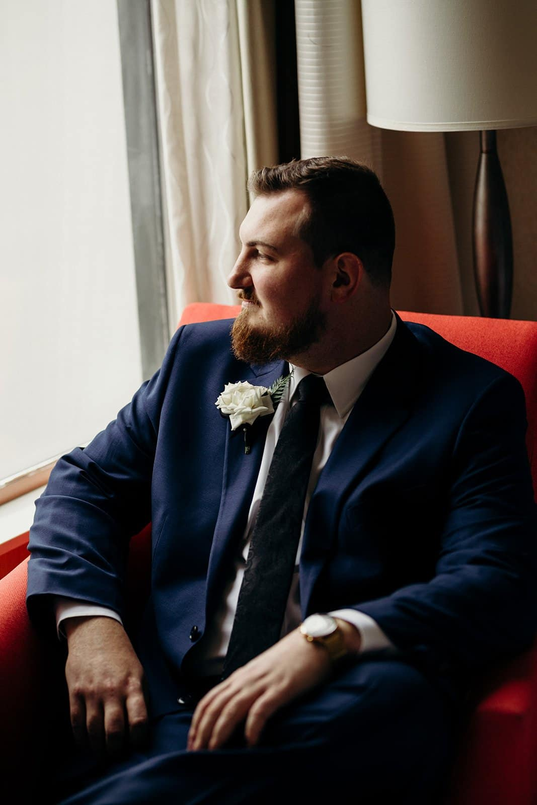 groom poses in red chair by window