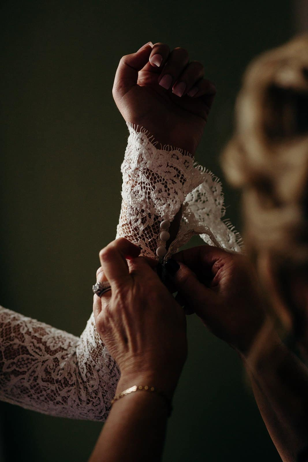 Woman helping bride put on jewelry