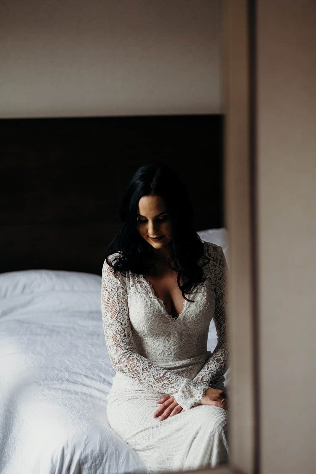 Bride waits on bed after getting ready for wedding