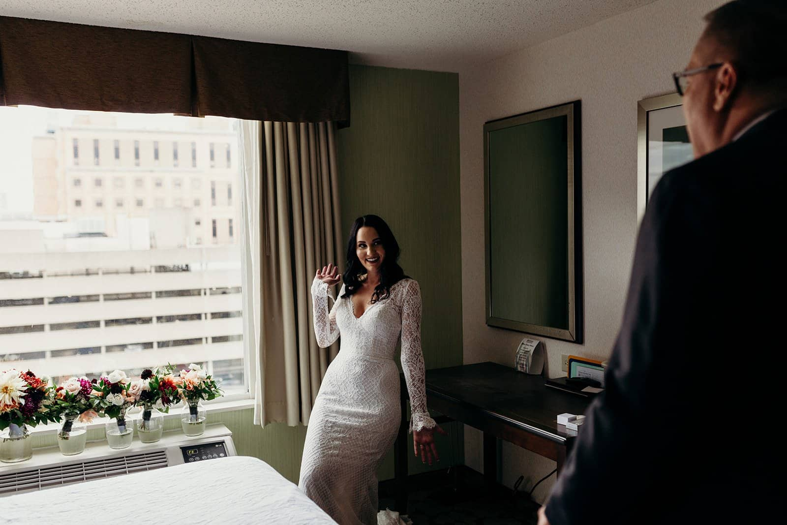 bride shows off dress to father