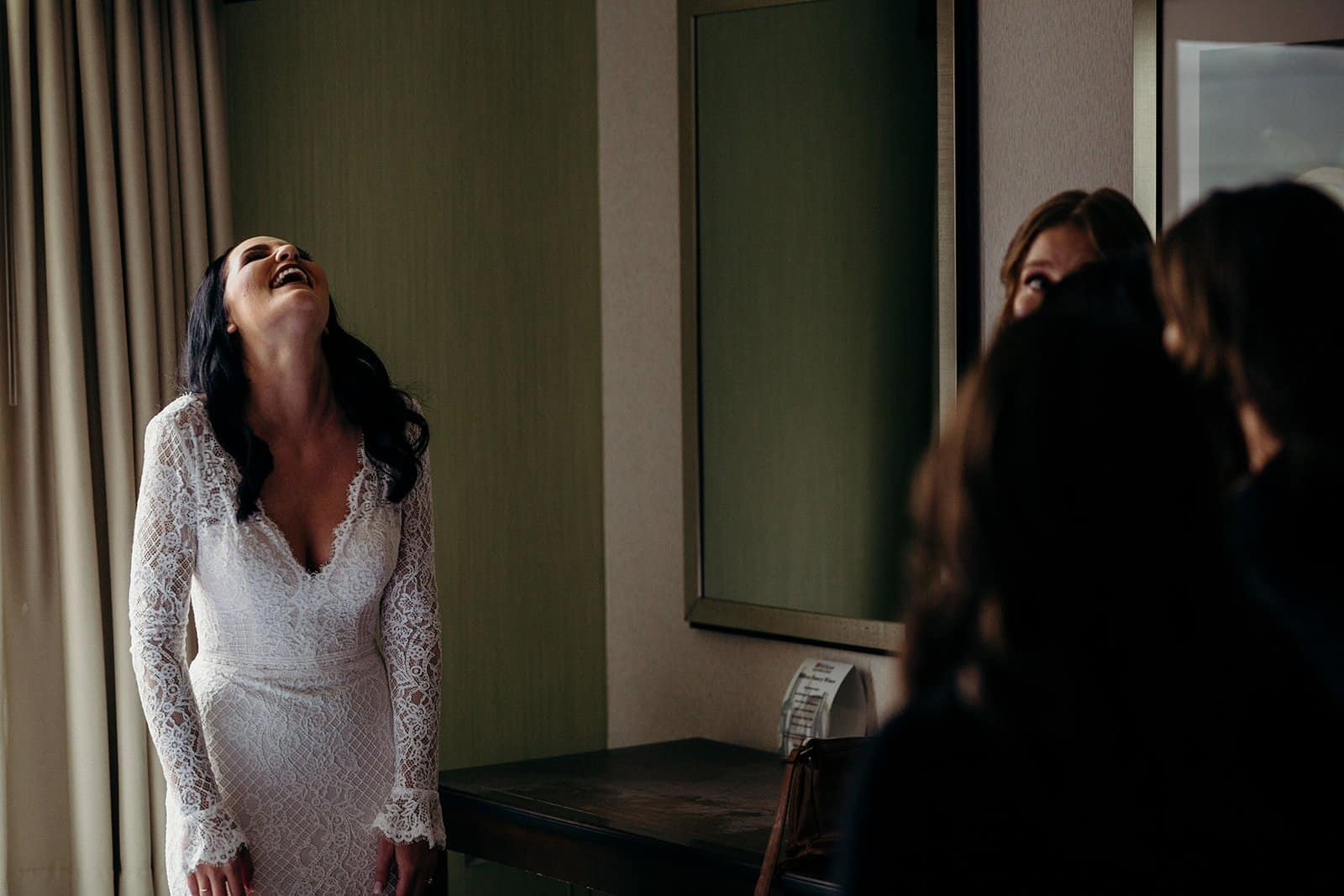 Bride laughs during bridesmaid first look