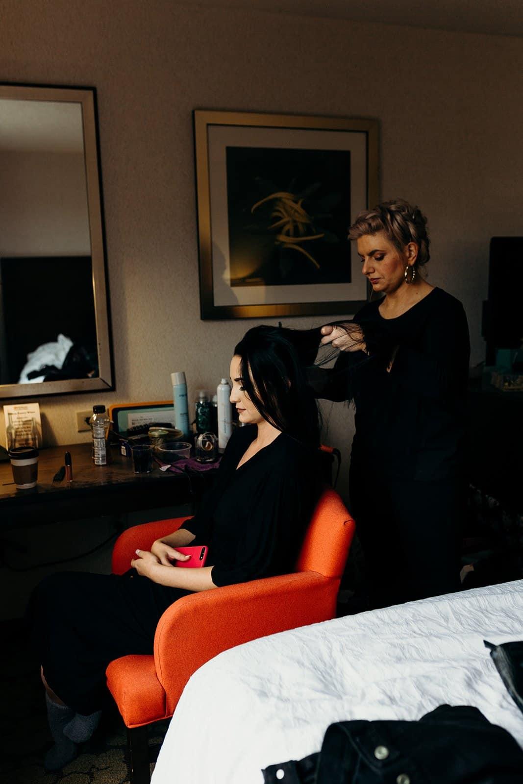hair stylist working on brides hair