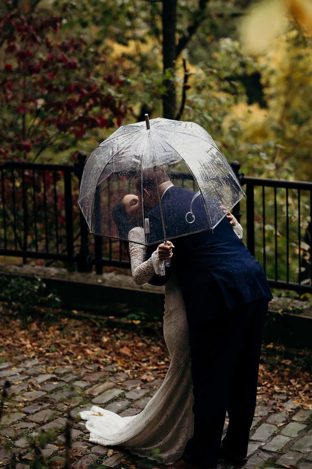 couple kisses under umbrella