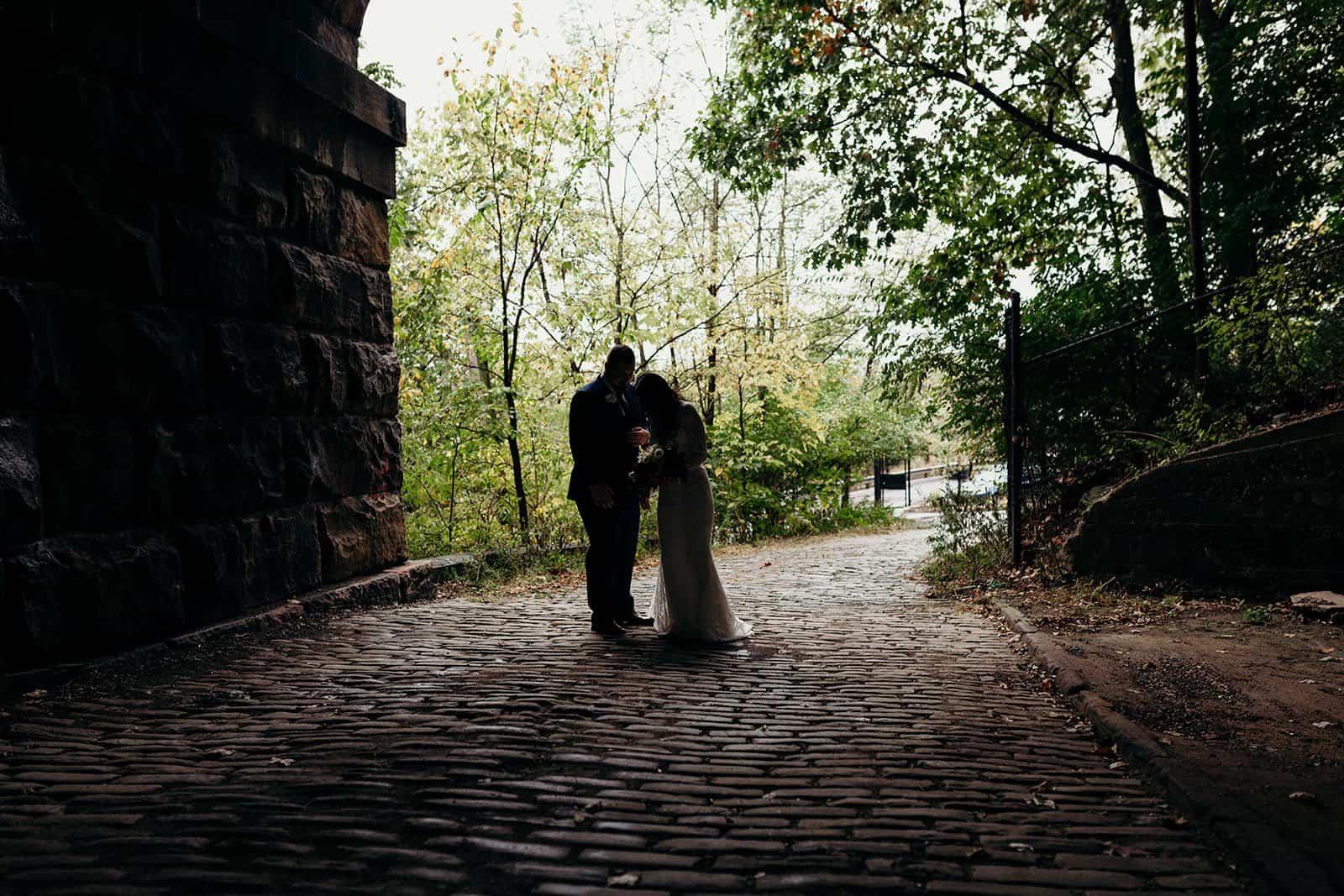 couple stands together in the dark under bridge