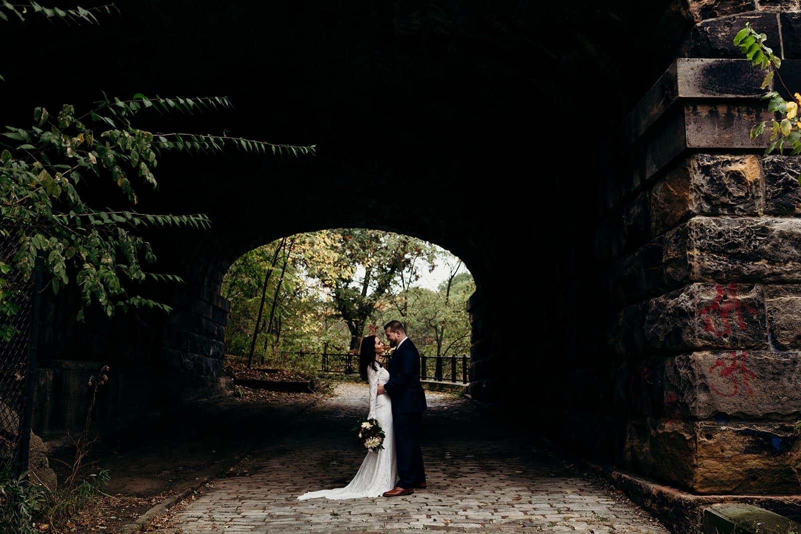 newly weds pose for photo under bridge