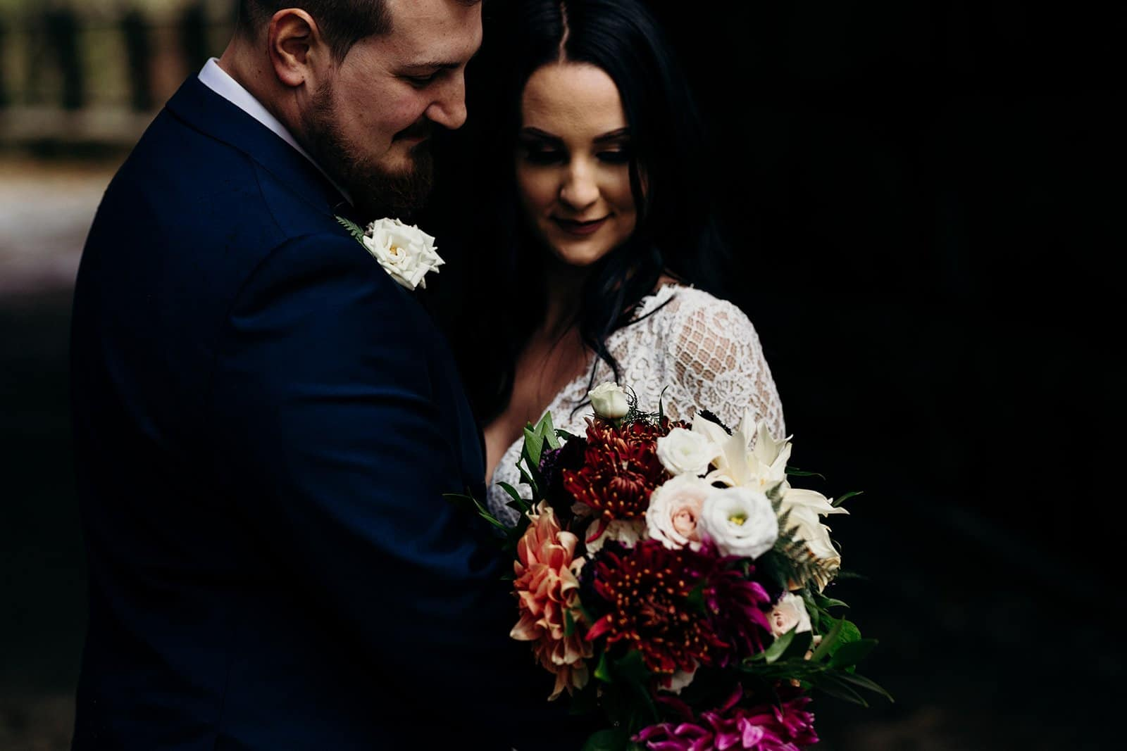 bride and groom look at bouquet