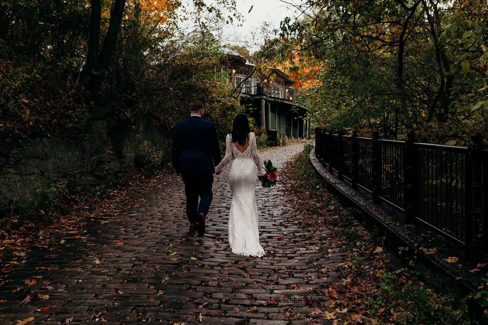 bride and groom walk away on brick pathway