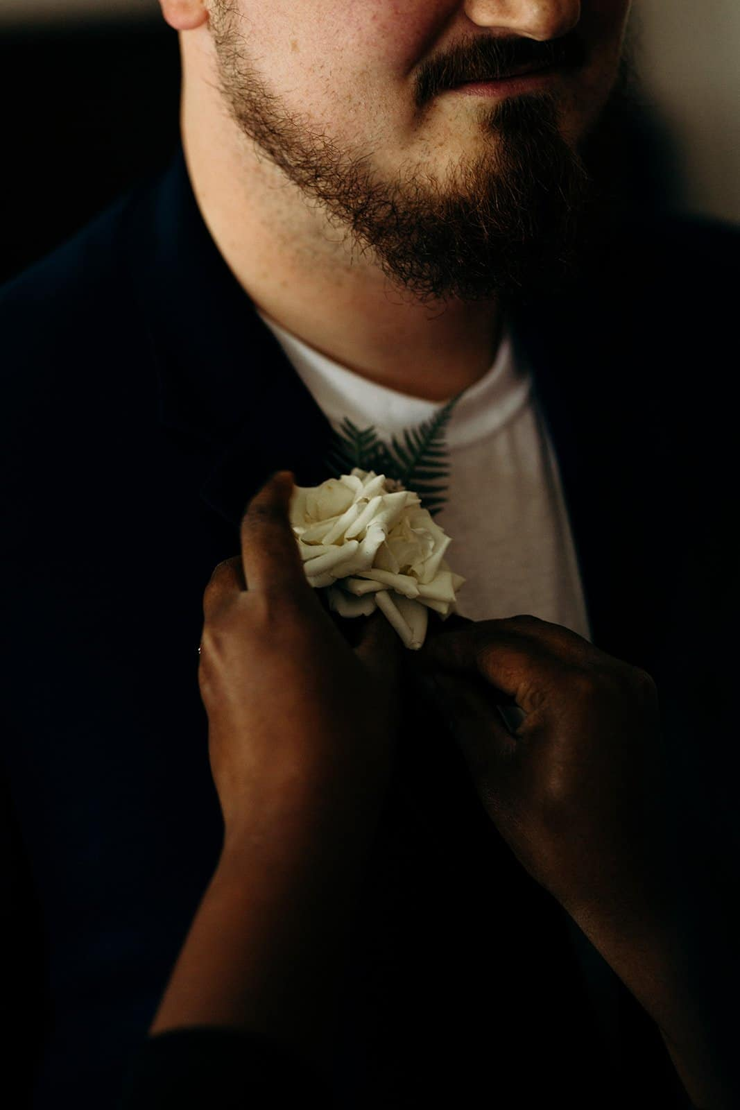 woman pins boutonniere on groom
