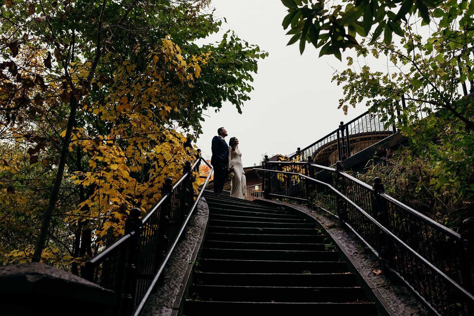 man and woman look up into the sky next to stairs
