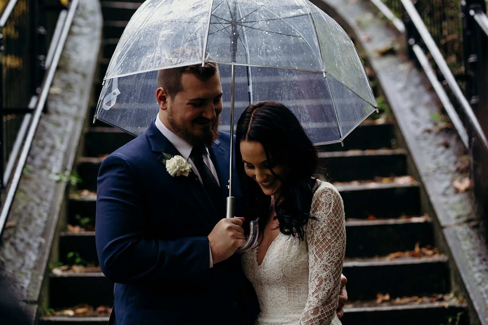 man holds umbrella for woman