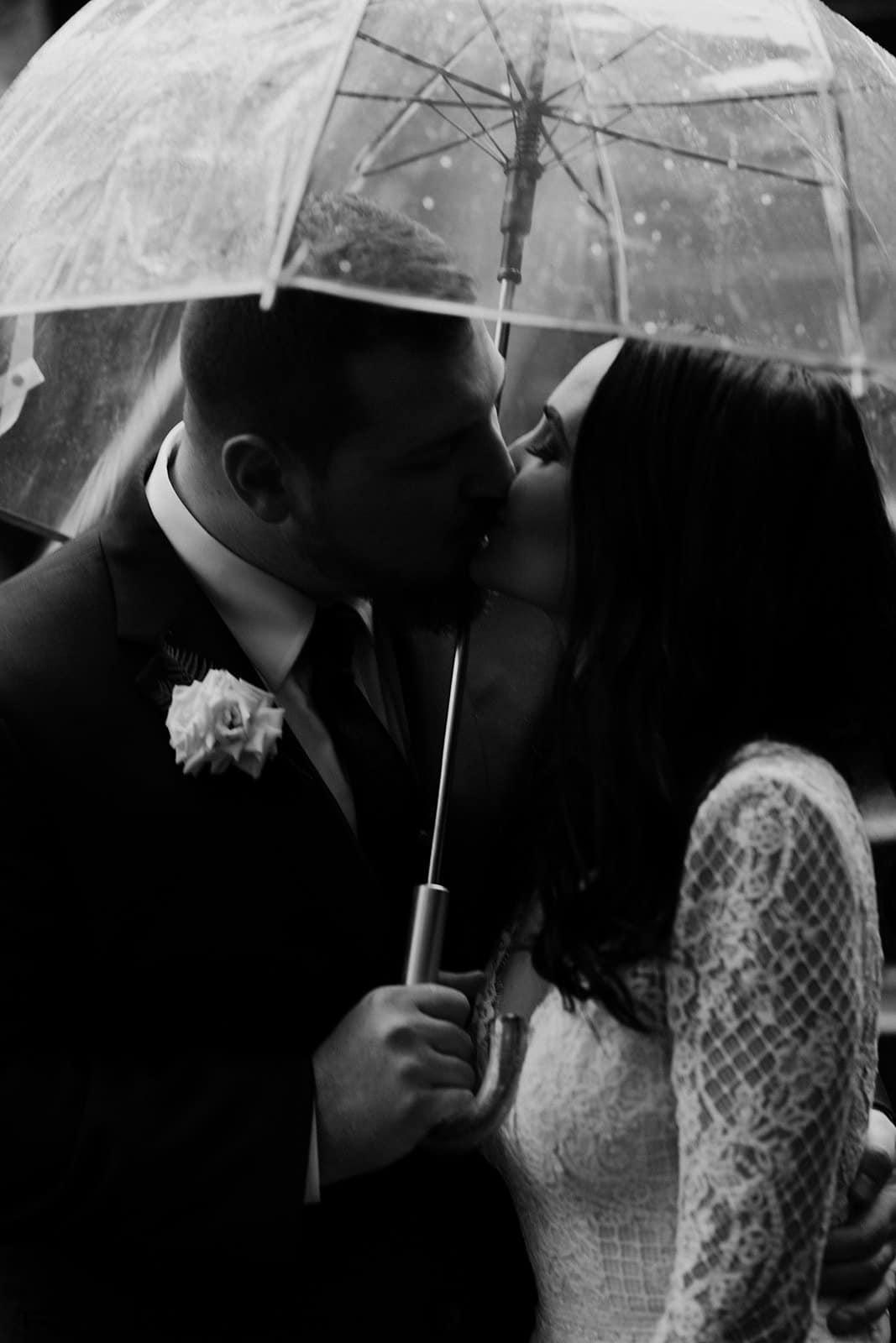 couple kisses under umbrella during the rain