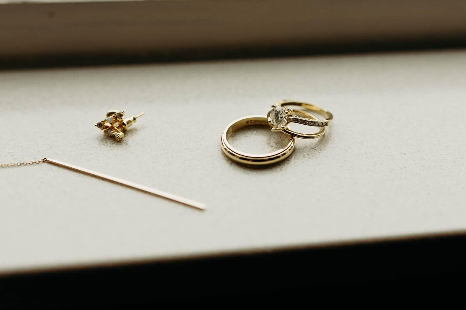 wedding rings and earrings on ledge