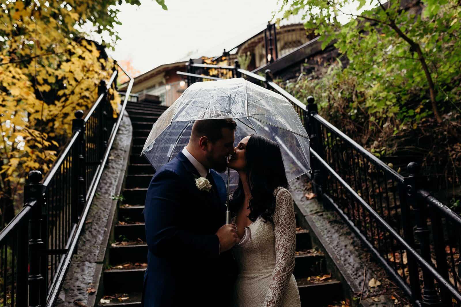 Husband and wife kiss under umbrella