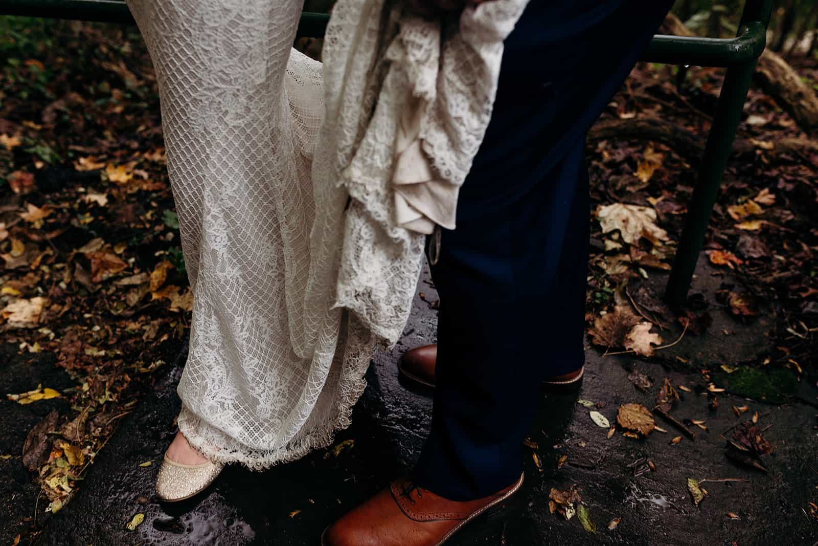 groom holds his bride's dress up from the dirty ground
