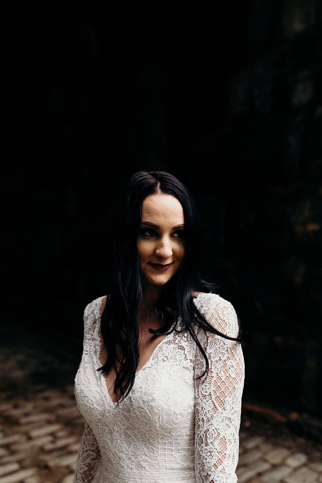 bride looks to the right with a dark background