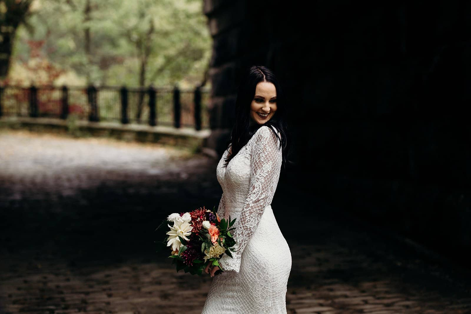 bride smiles and looks over her shoulder while holding flowers