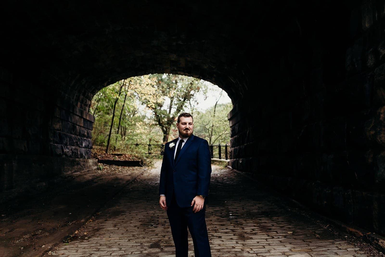 groom stands alone under dark bridge