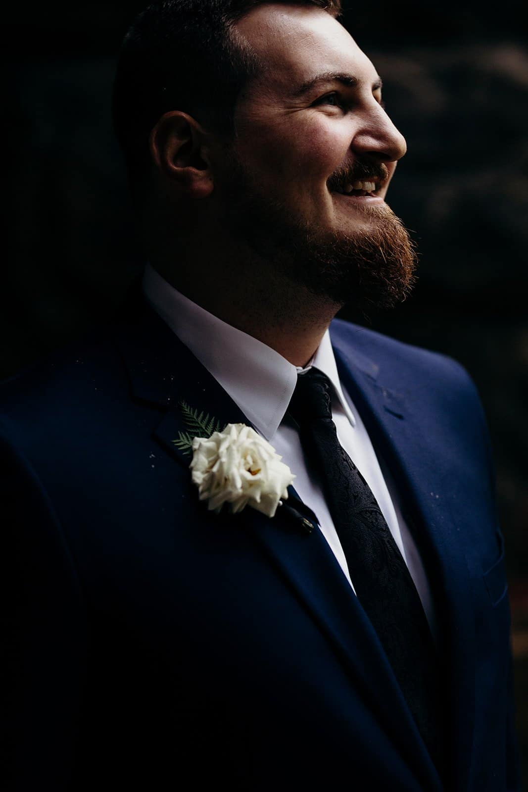 groom smiling and looking into the light