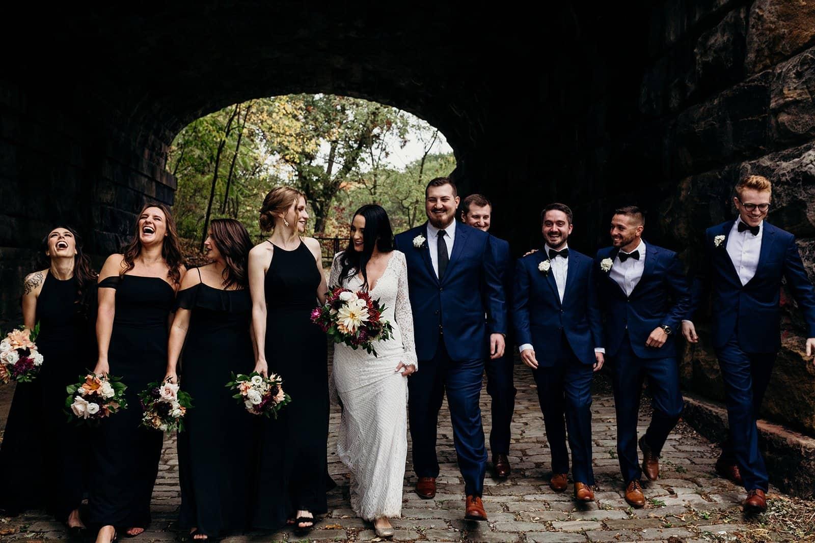 bridal party walking under covered bridge