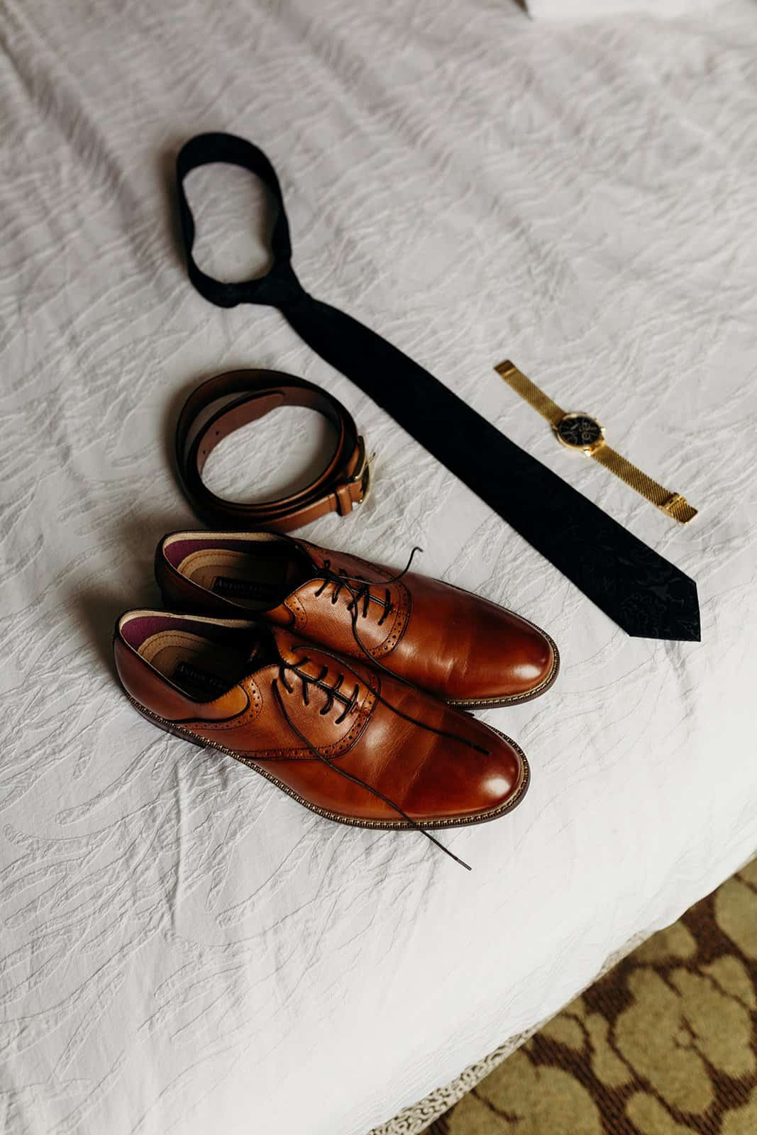 Shoes, tie, belt and watch on bed
