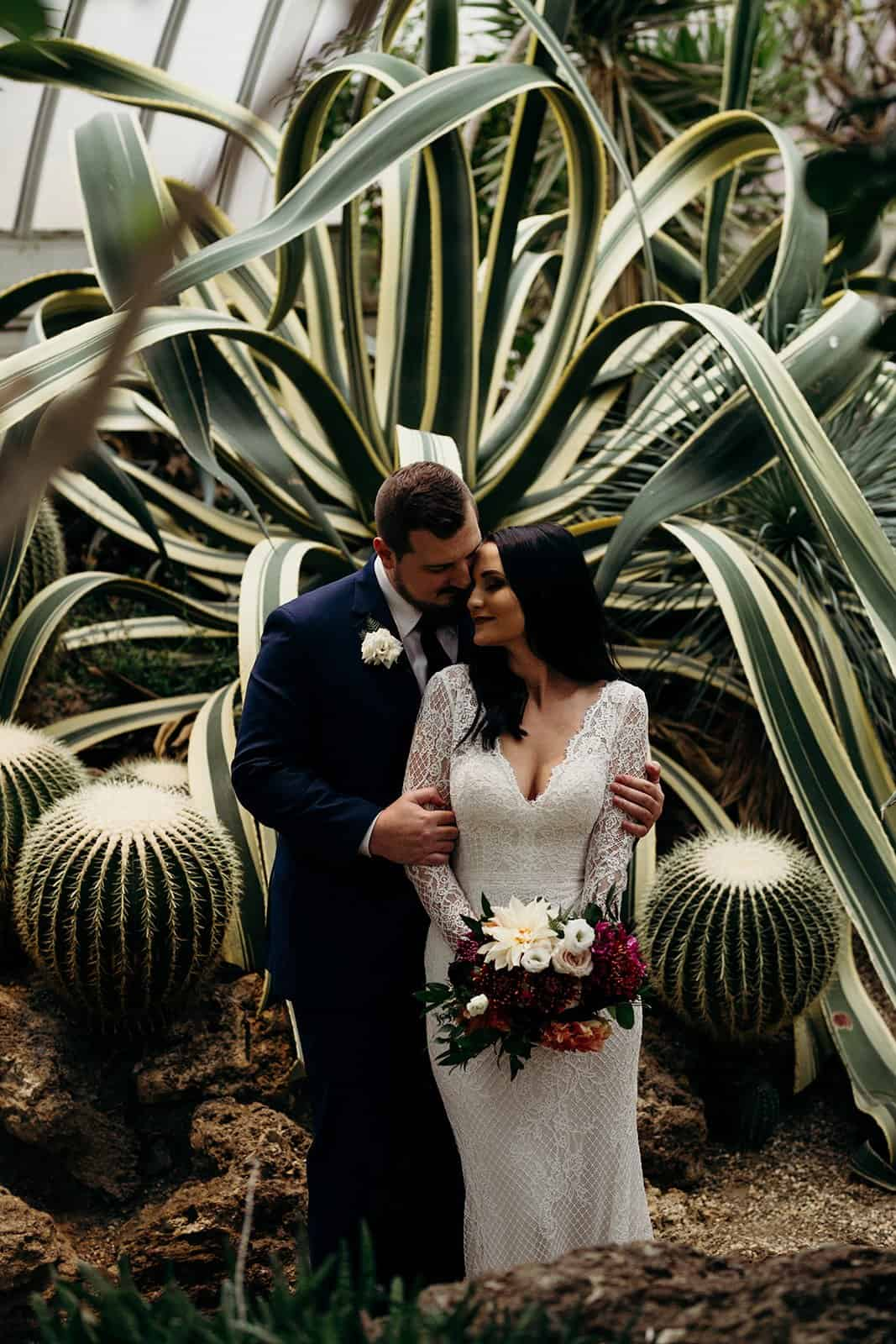 Bride places forehead on groom next to a cactus