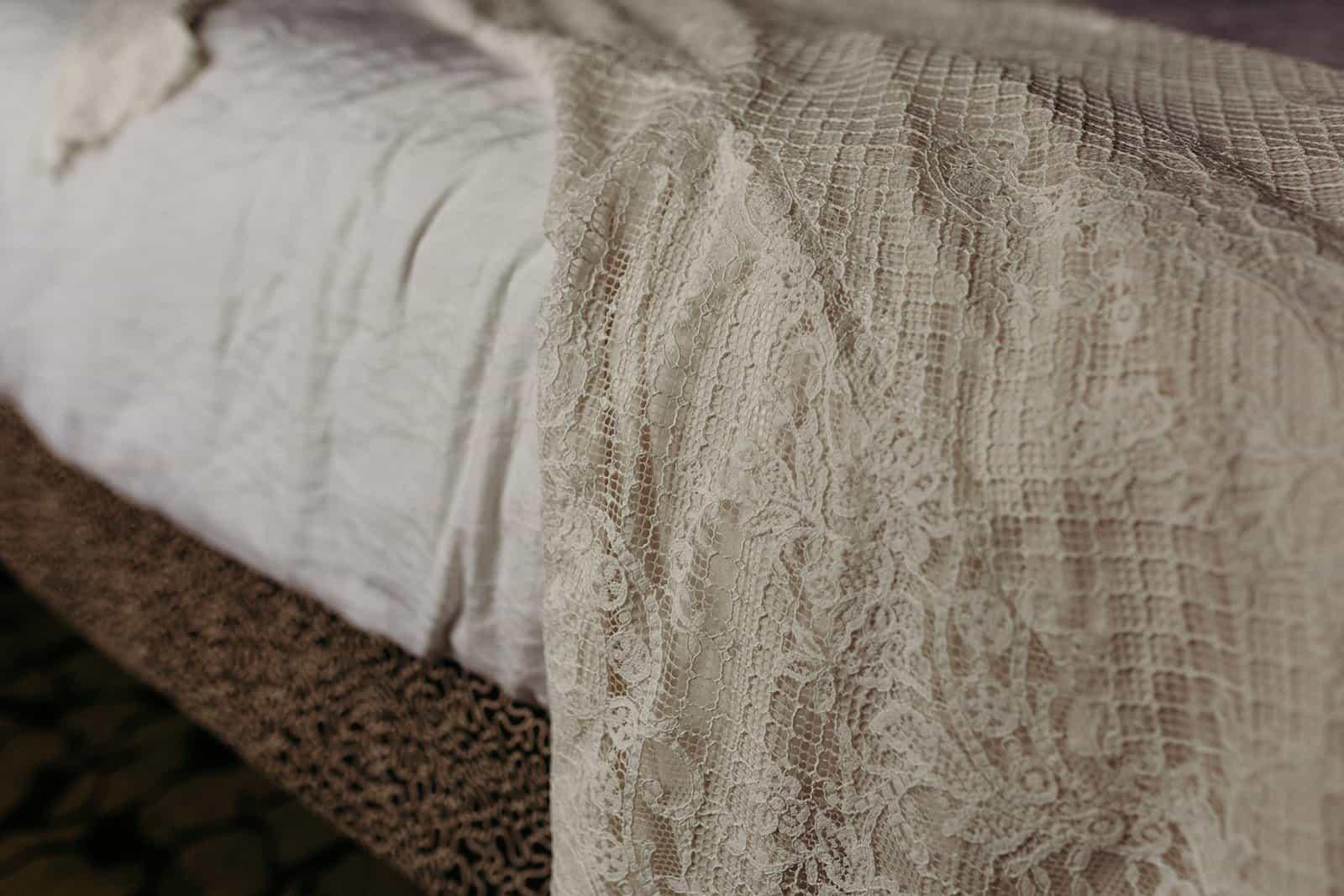 Detailed shot of wedding dress on bed