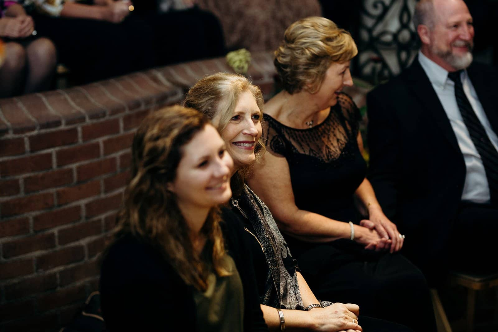 three women smile and laugh during ceremony