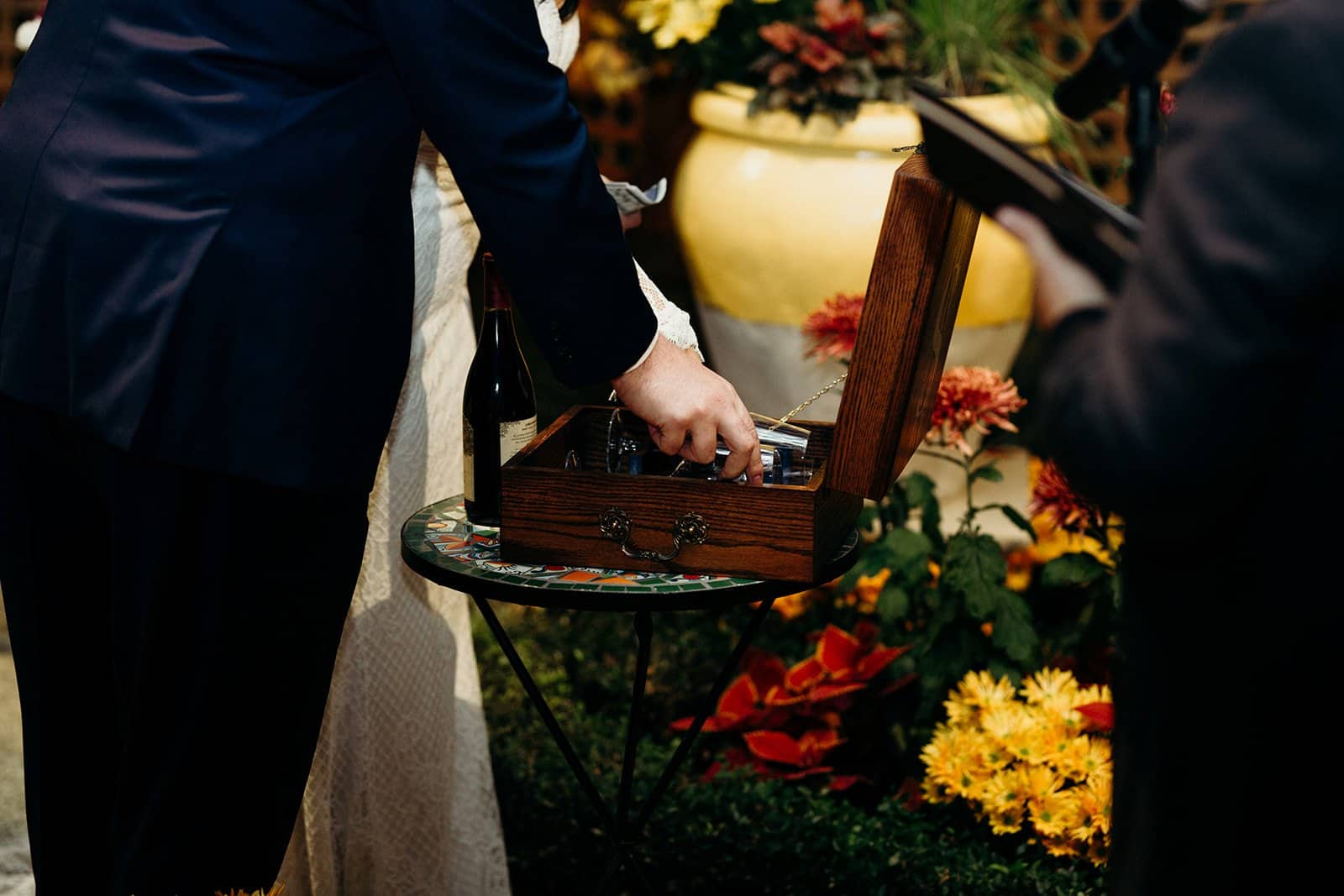 hand placing memories into a box during wedding