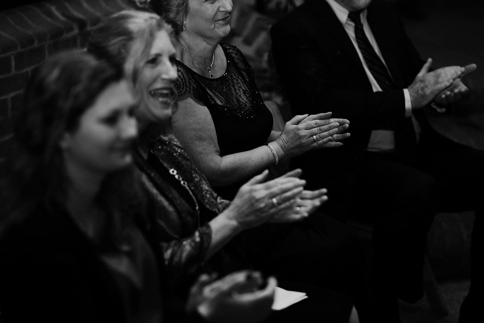 three women clap during wedding