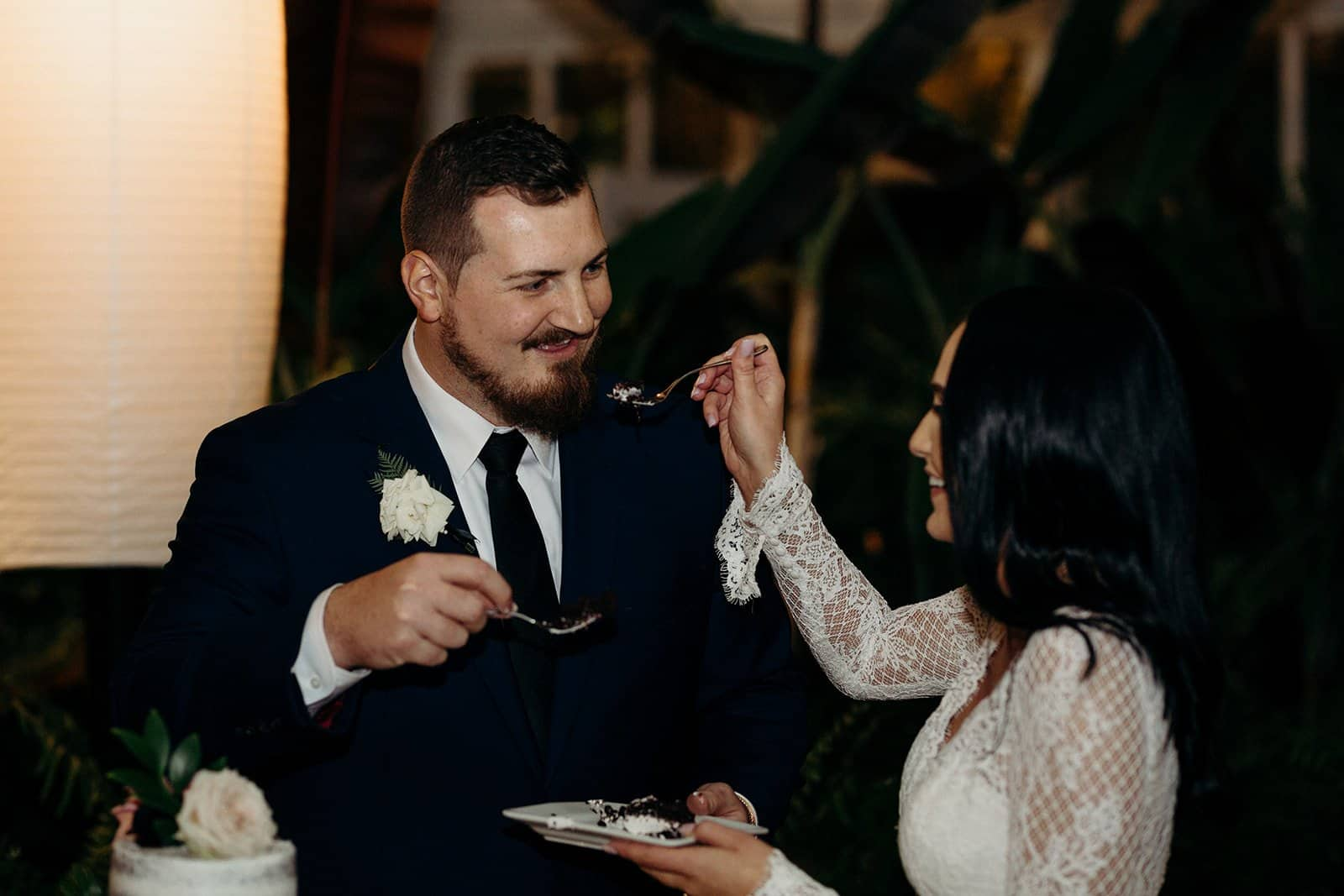 Groom smiles at bride as she feeds him cake