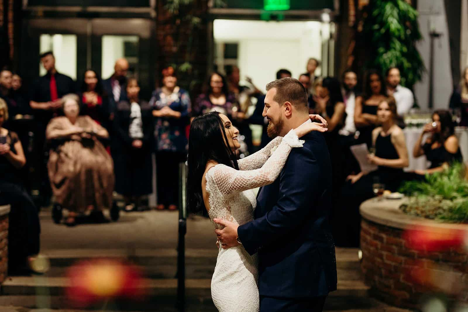 Family watches in the background while newly weds dance