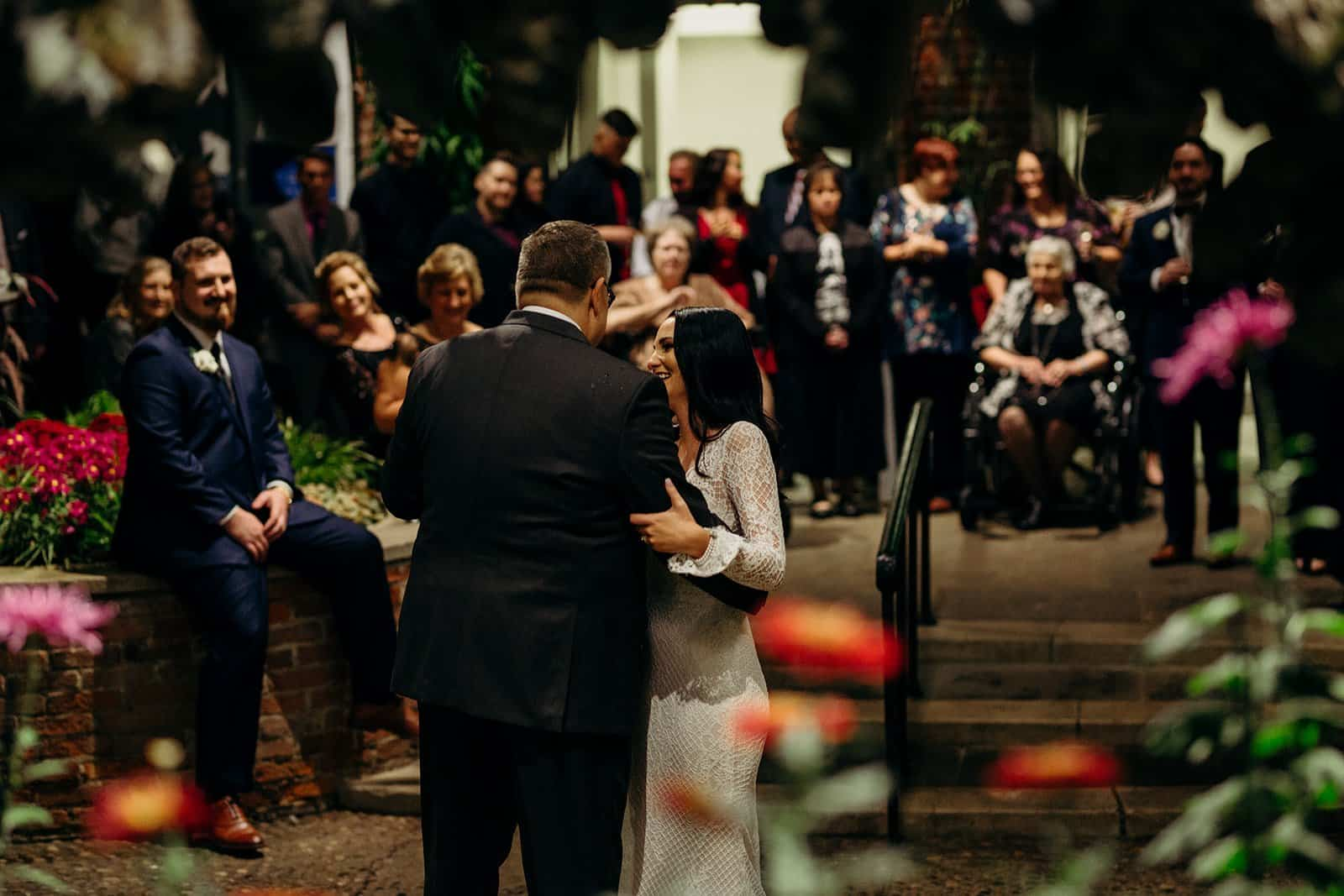 Groom smiles at bride and father during first dance