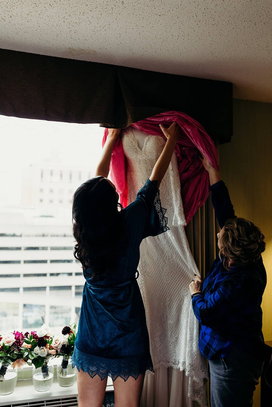 Bride and mother look at wedding dress