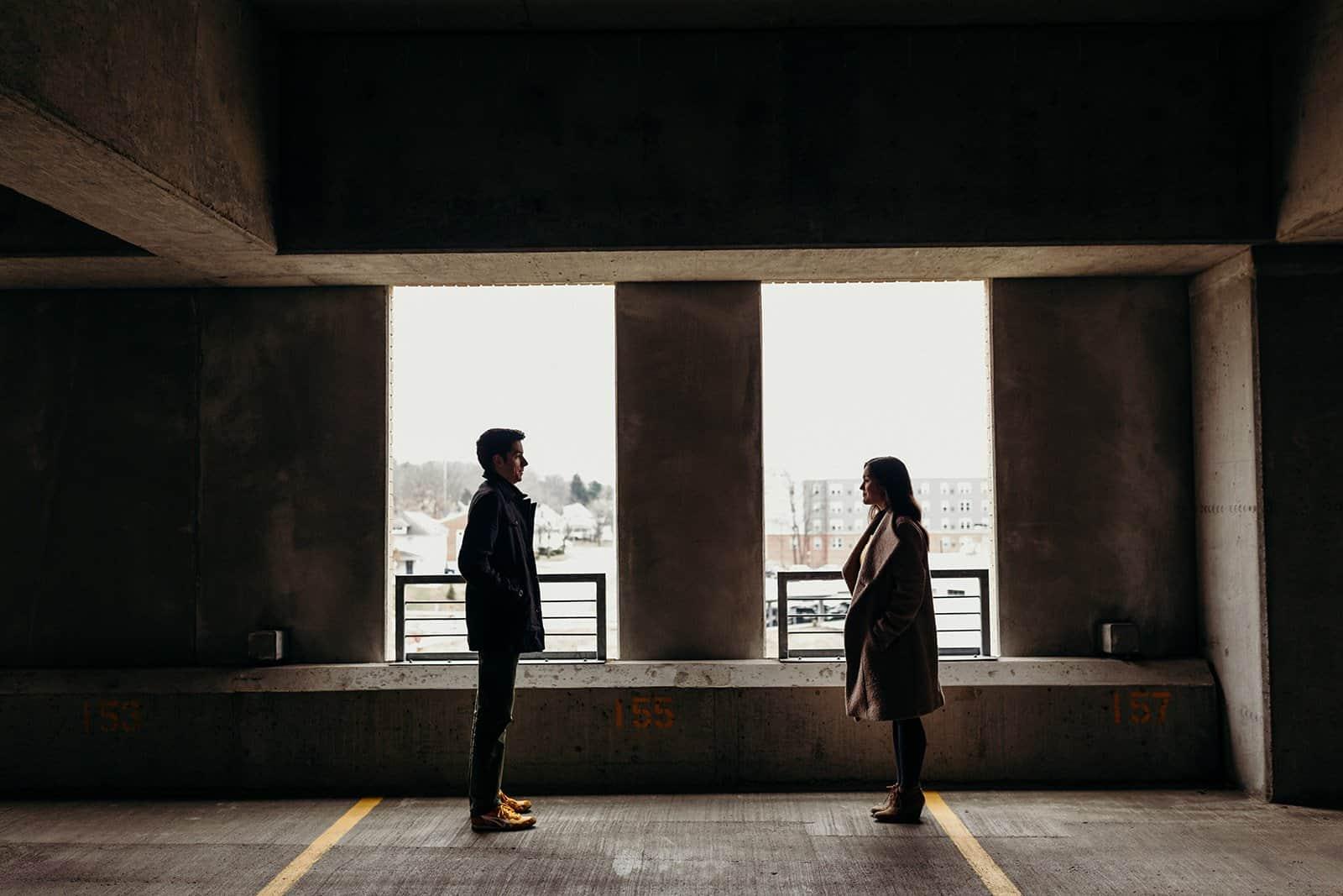 Kent Ohio Engaged couple facing each other in parking garage windows