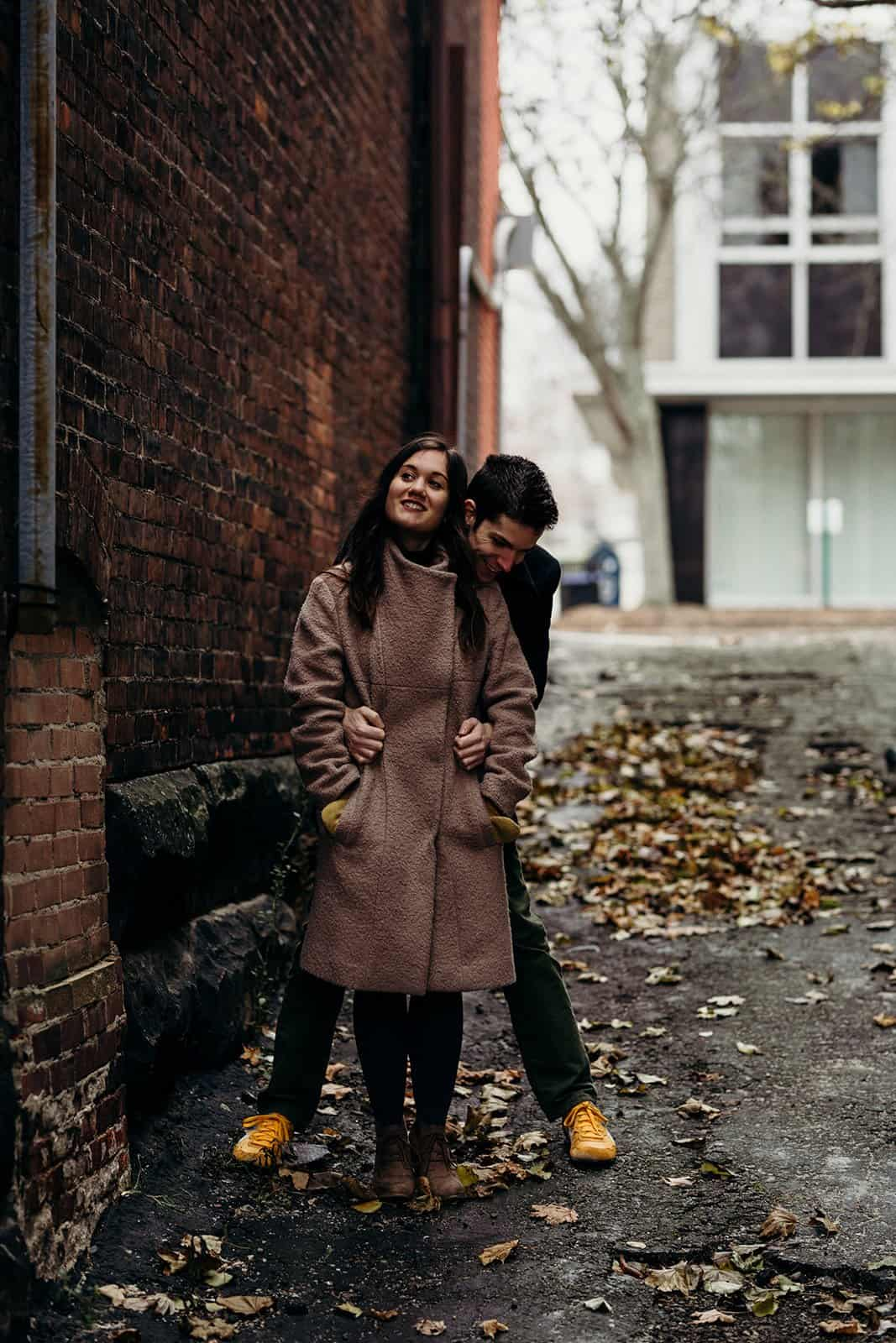 engaged couple pose in alley in Kent Ohio