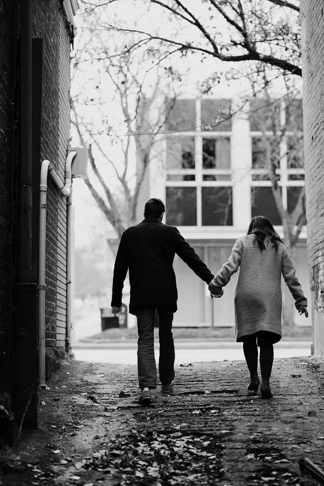 engaged couple hold hands walking in alley in Kent Ohio