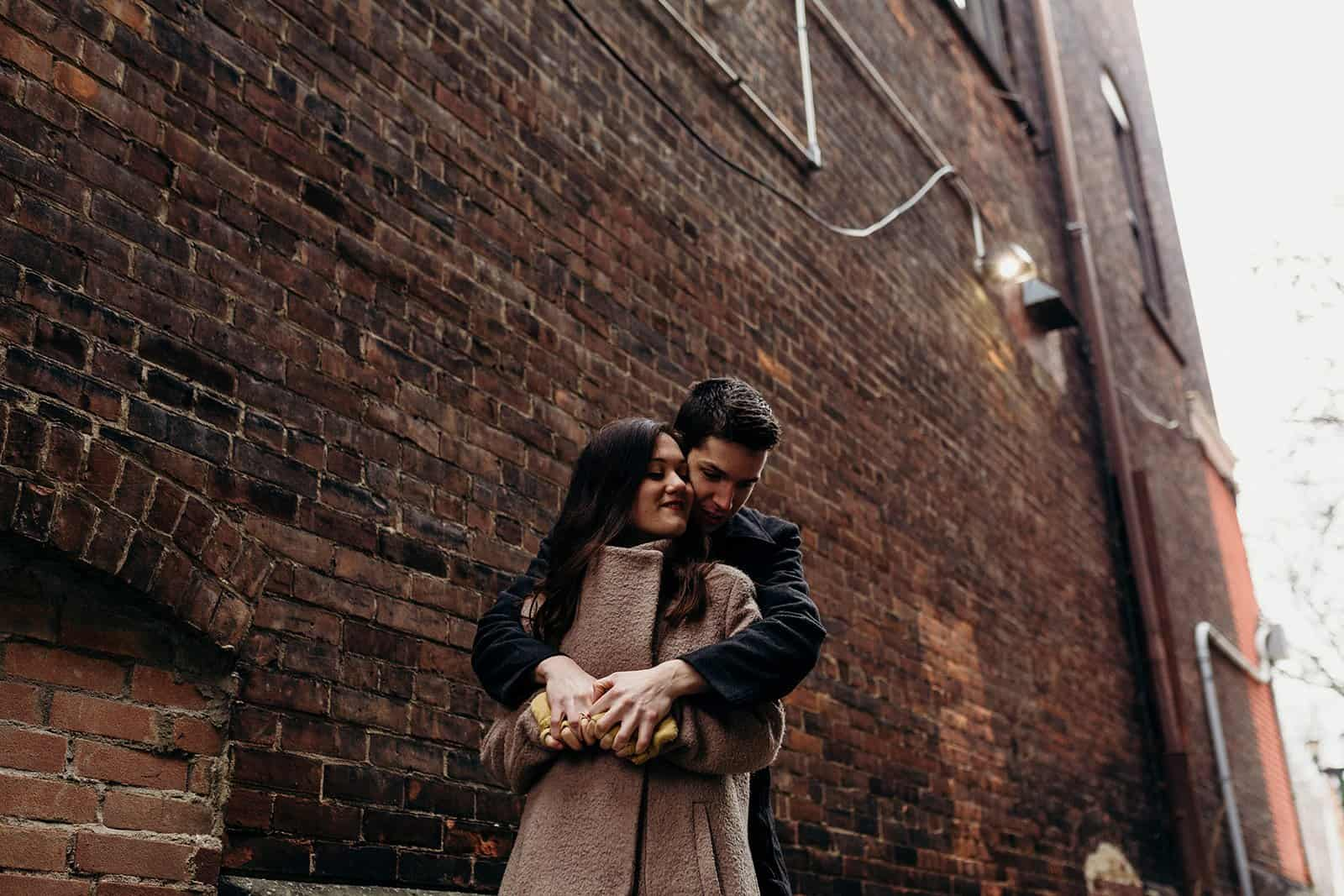 Man and woman embrace in alley in Kent Ohio