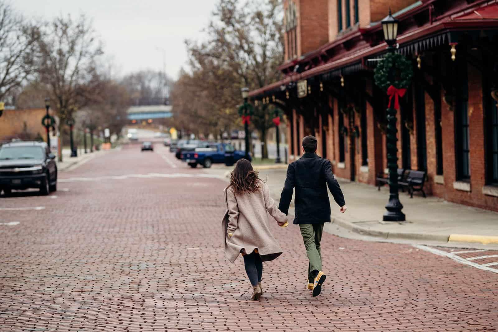 Man and woman run down brick street in Kent Ohio