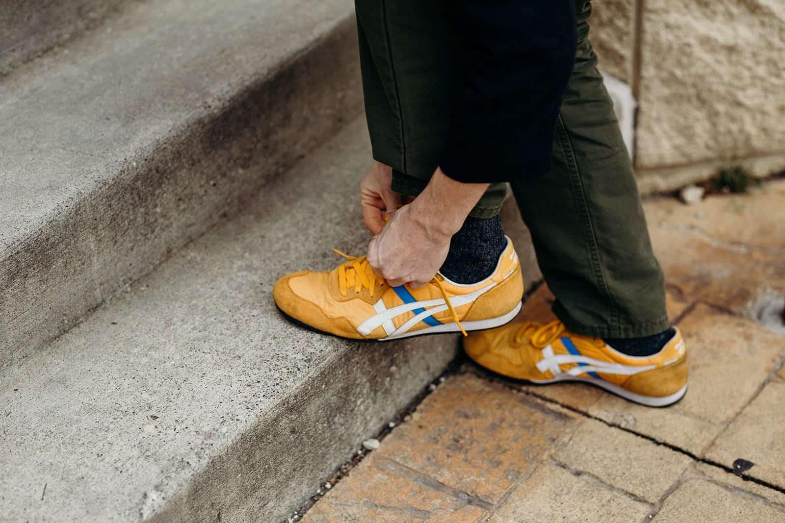 man tying yellow shoe in kent ohio