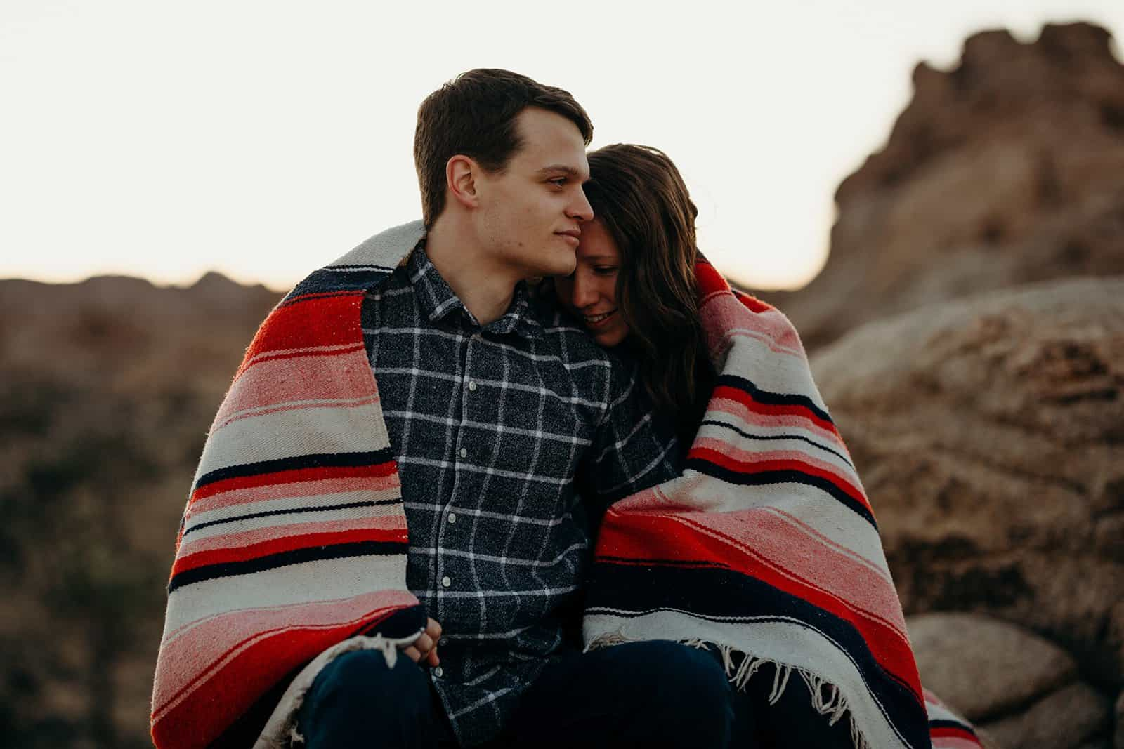 Couple cuddling and wrapped in blanket on Joshua Tree Trip sunrise