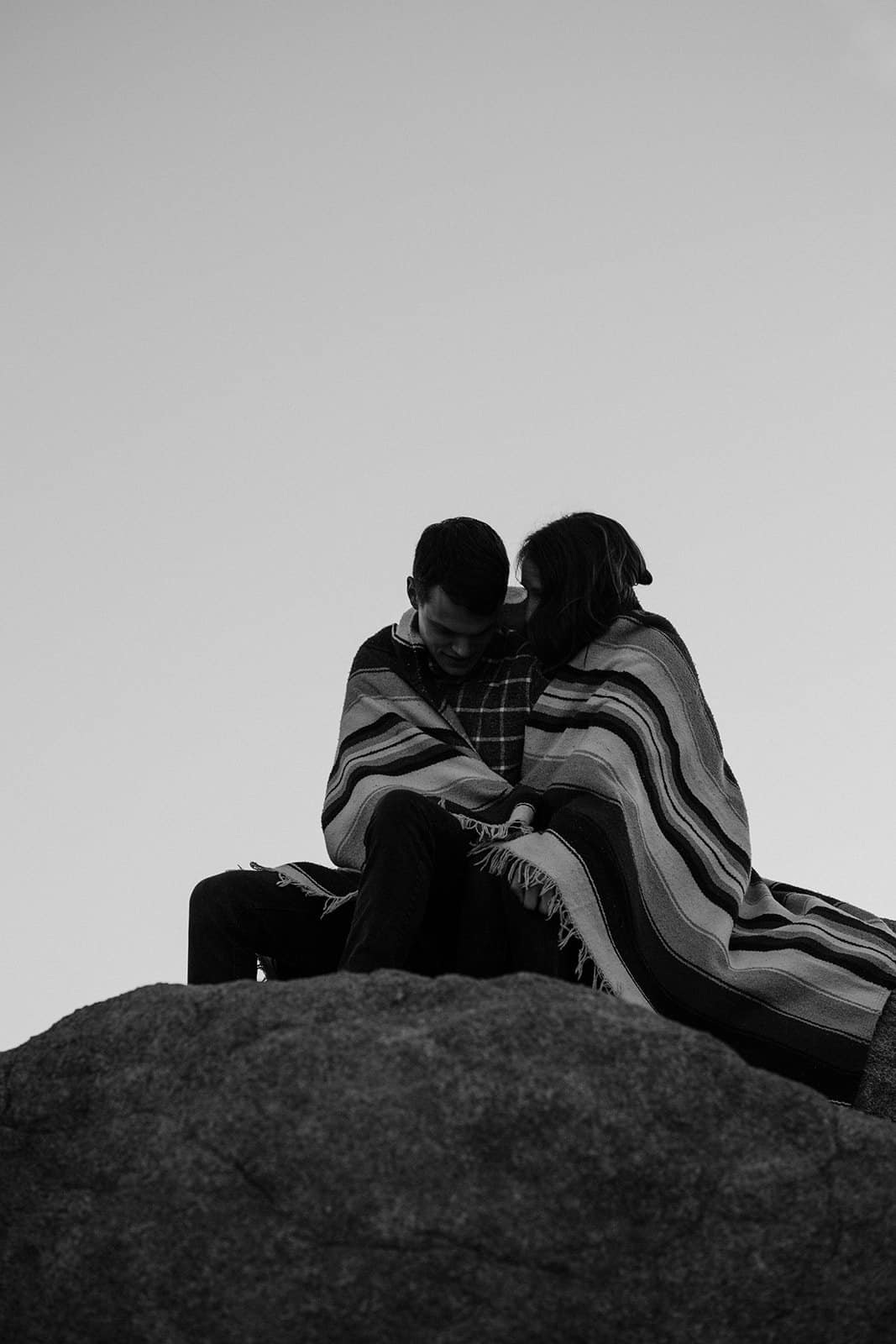 Couple wrapped in blanket on Joshua Tree Trip sunrise