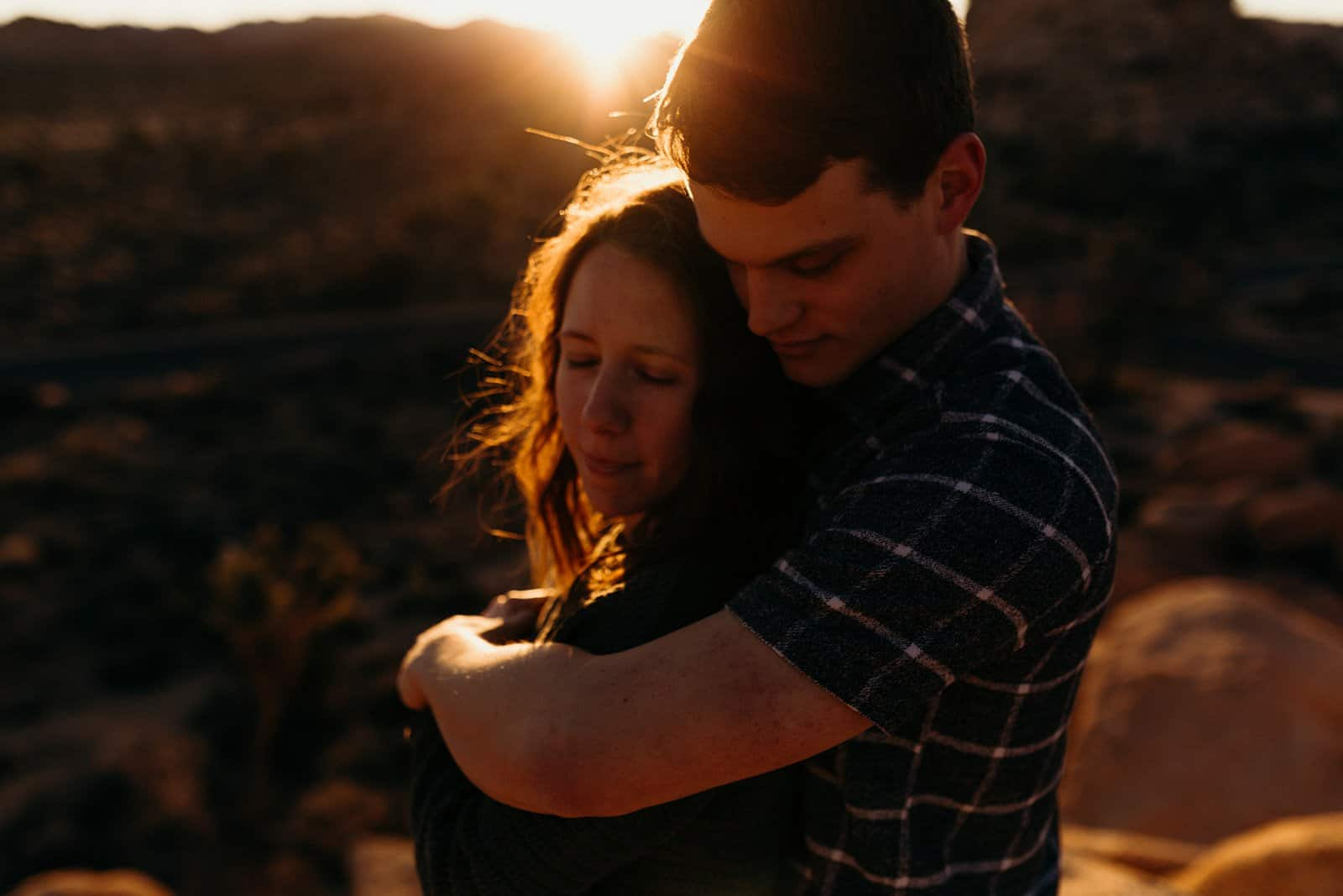couple embracing in Joshua tree with sun flare