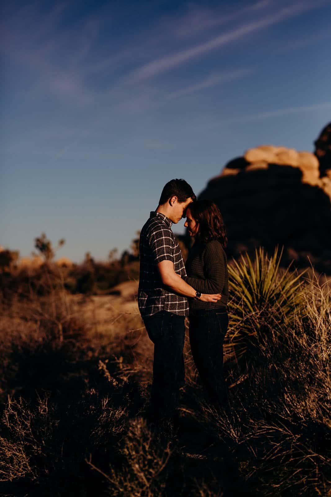 couple standing among Joshua Trees