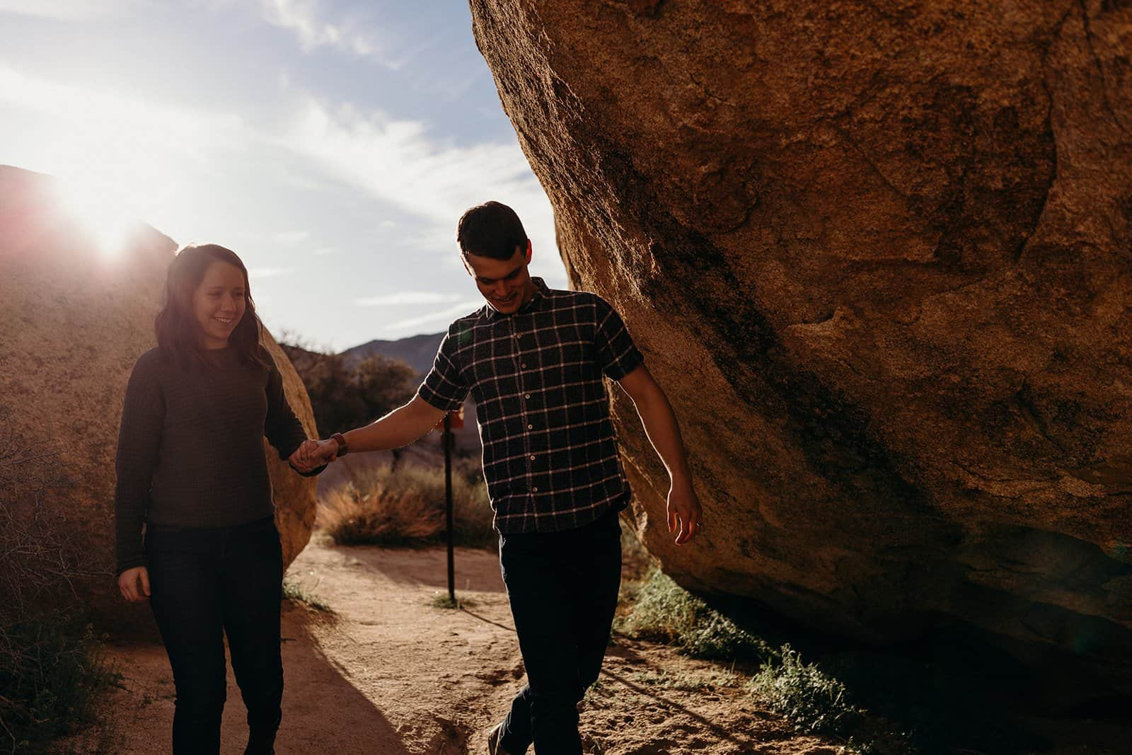 Couple laughs and walks towards cavern in Joshua Tree National Park