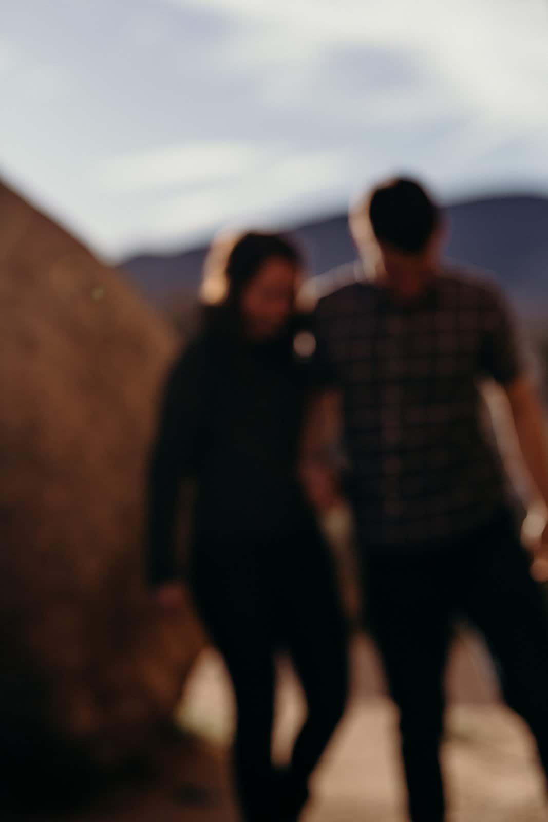 Couple walks towards cavern in Joshua Tree National Park